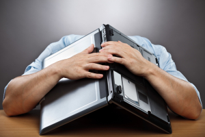 exhausted-businessman-covering-his-head-with-his-laptop_pop_15451